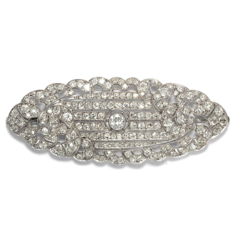 Typical of the 1920s and early 1930s, this brooch takes the shape of a flat shield set with numerous diamonds, amounting to 7.30 ct altogether. Graphic lines structure the central area, surrounded by a scalloped edge that lends a certain softness to