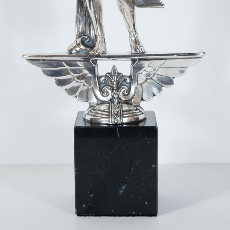 This Art Deco sculpture was realized in the United States, circa 1930. It features a perfectly proportioned male figure wearing gladiator sandals; a flowing robe; and a loin cloth- all in silvered bronze. He holds a scroll in his left hand, while