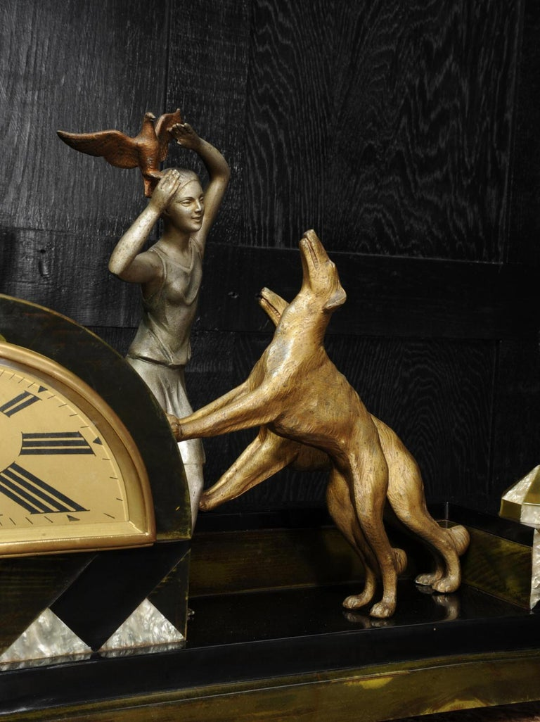 A stunning and rare clock by the well known sculptor Pierre Sega, circa 1925. It features a charming scene of a girl holding a bird aloft to save it from her two large and playful dogs. Beautifully modelled in colored and patinated white metal. The