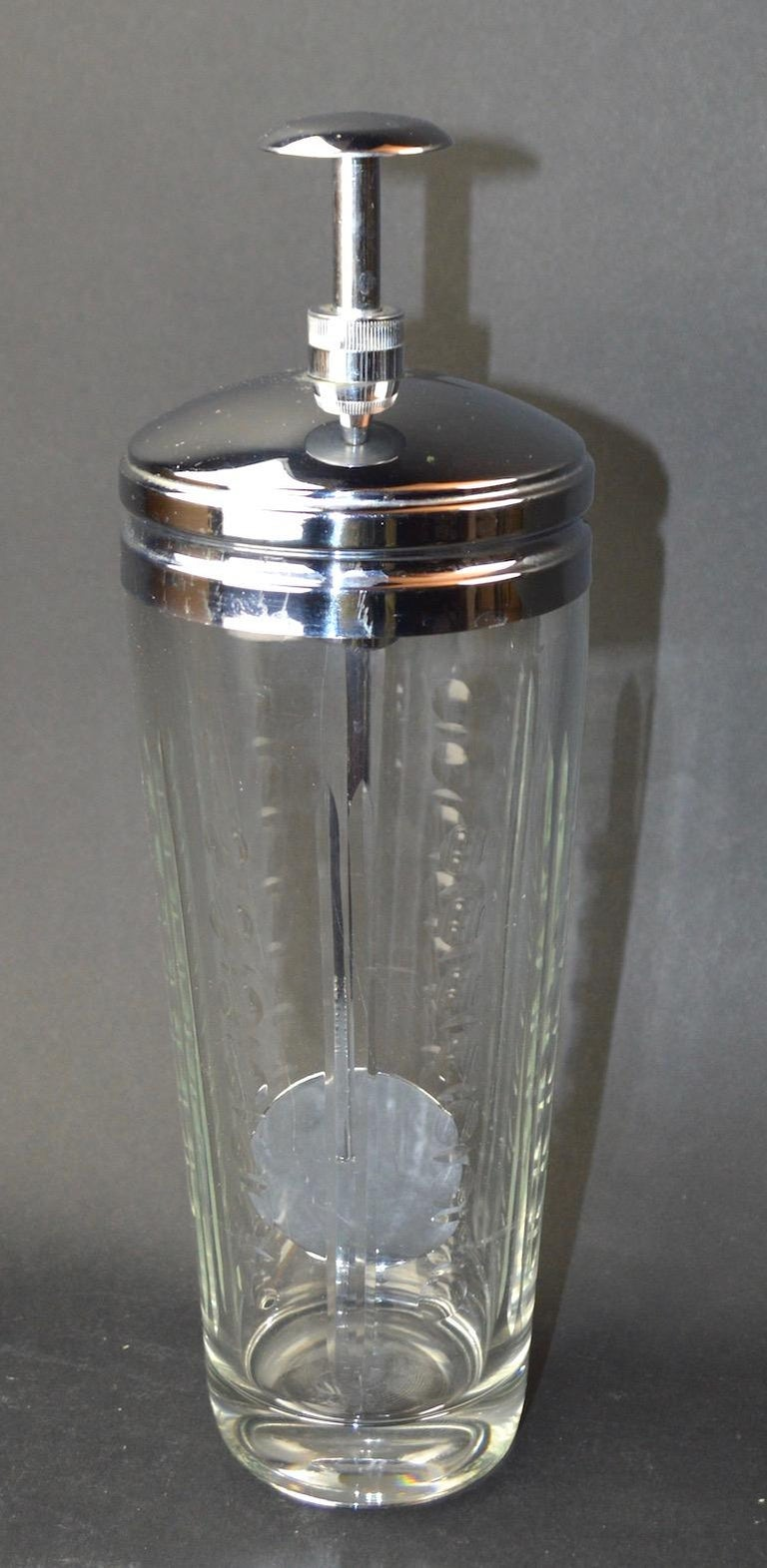 Etched and pressed glass body with bright chrome CAP and mechanical twist mixer element. Push the top knob down and the chrome paddle will spin, making the perfect mixed drink every time. Great novelty item form the Machine Age period, bears pat.