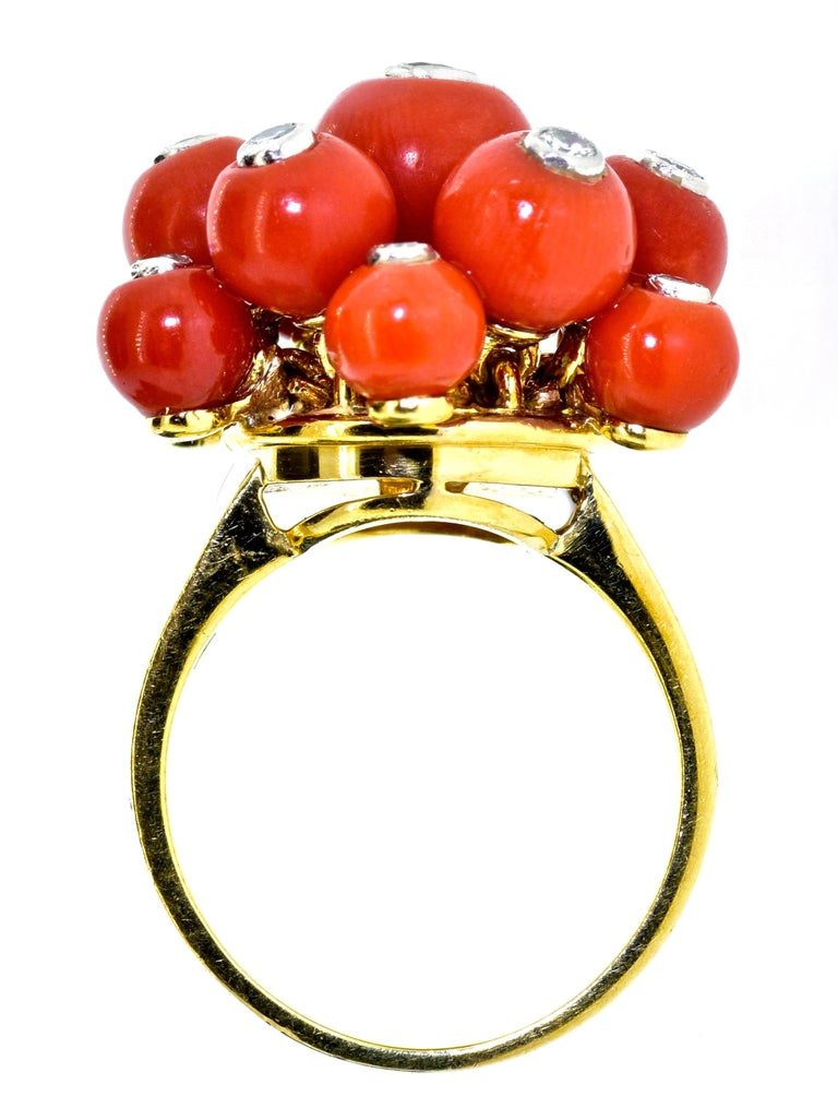 Art Deco coral, diamond, 18K yellow gold and platinum unusual ring bearing European cartouche stamps (probably French) that are difficult to read.  This ring has 13 natural vivid orange coral spheres of varying sizes with platinum tube set round
