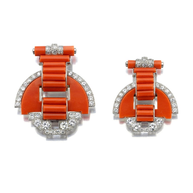 A cloak clasp convertible to clip brooches, each designed as a series of geometric shapes composed of coral batons, flat coral segments, and round diamonds, one clip slightly larger than the other, the clips combine with a chain of diamond and coral