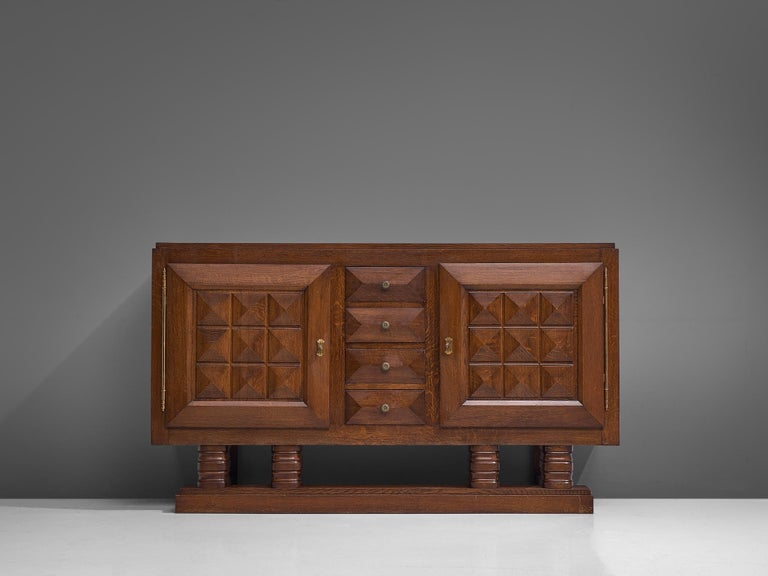 Gaston Poisson, credenza, stained oak, France, 1930s.   Sturdy sideboard in oak with graphical door panels and drawers. The sideboard is equipped with several shelves and four drawers which provide plenty of storage space. The door panels and base