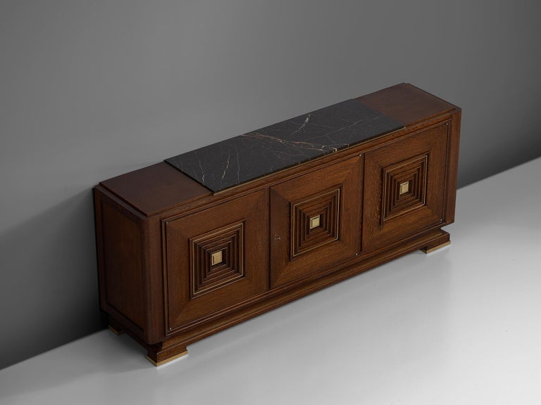 Credenza, in oak, marble, and brass, France, 1930s.   Large Art Deco sideboard in the style of Maxime Old. This heavy, almost Brutalist, credenza seems to float on its elegant base with stunning brass detailing. The credenza is equipped with three