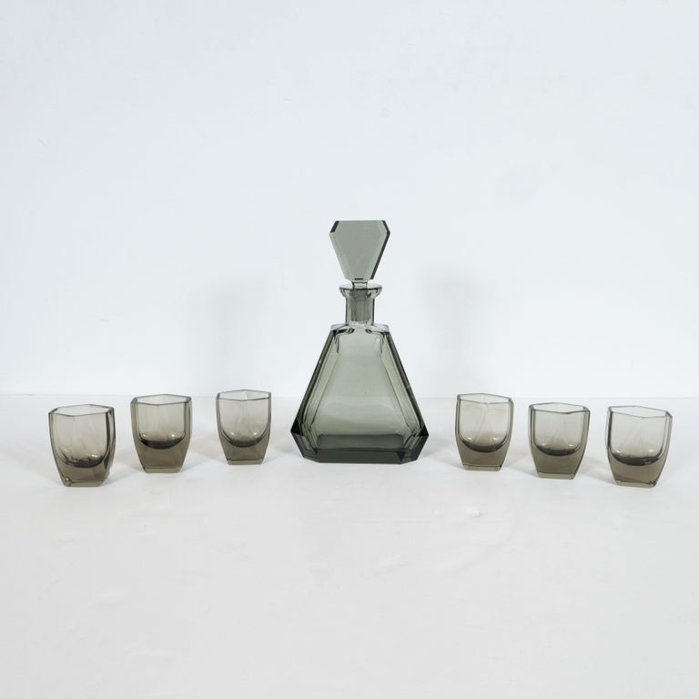 This elegant Art Deco machine age decanter set was realized in the Czechoslovakia, a country renowned for its superlative glass production during this period, circa 1935. It features a faceted decanter with its original stopper in sultry translucent