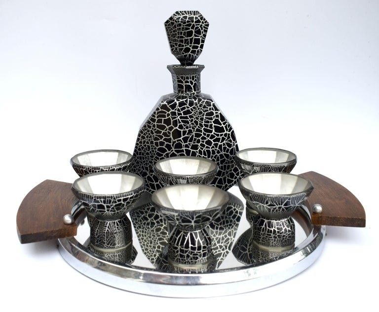 Superbly stylish Art Deco decanter set dating to the late 1920s-1930s made in the Czech Republic. This set features a large impressive decanter with stopper and six matching conical shaped glasses. The whole set is black enameled with silver overlay