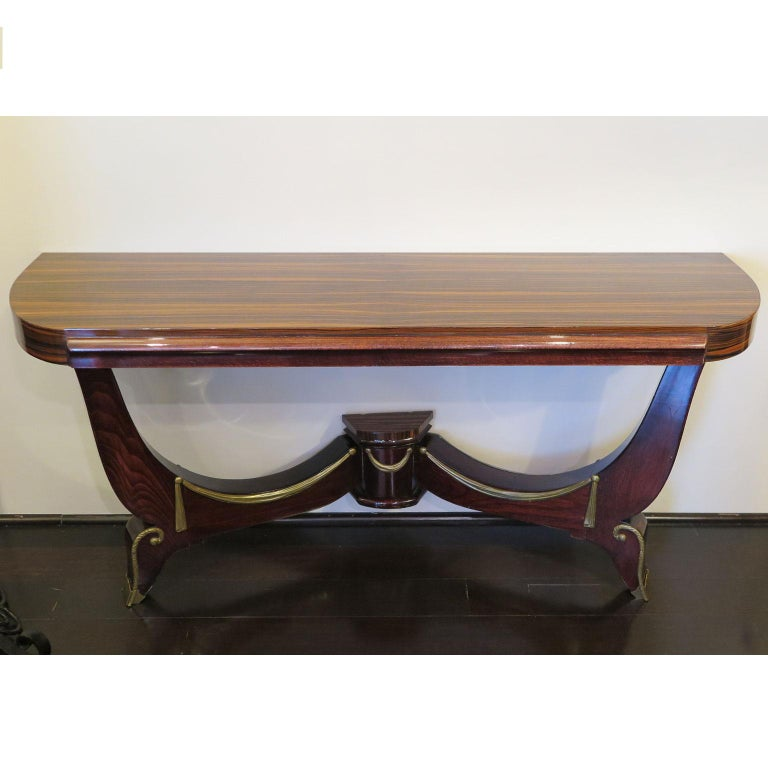 Classic Art Deco console showcases a demilune top. The top and base detail is done in Macassar while the curved legs and front apron are in a Mahogany. The curved base features brass details in the style of tassels and swirl details on the feet with