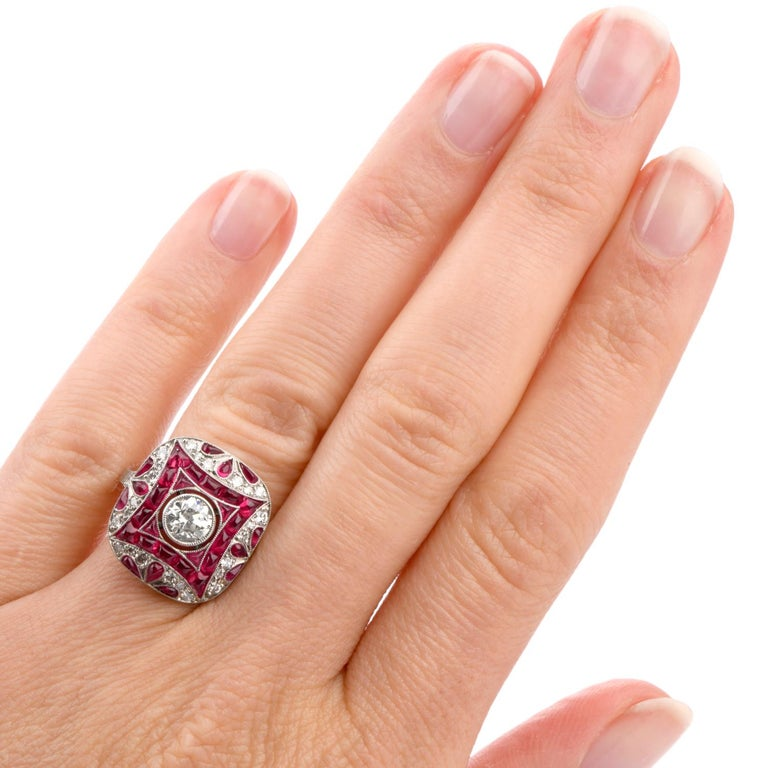 Discover the magic of the past with this stunning and vibrant Art Deco inspired Ruby and Diamond  cocktail engagement ring crafted in Luxurious Platinum.  Featured in the center of this motif is one round faceted old European-cut diamond  weighing