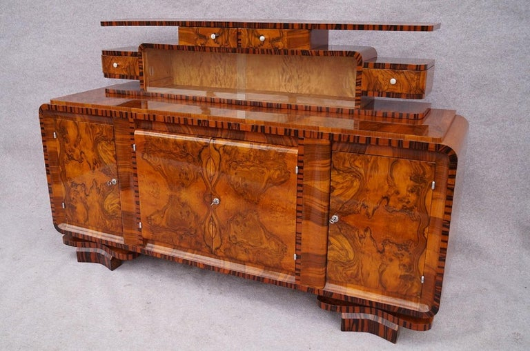 We present Art Deco designer dining room from Cracow, Poland, 1930.  The set includes:buffet, dresser helper for the buffet, glass-case , table add six chairs. Walnut wood was used to make the furniture, and as well as Macassar wood wenner. Every