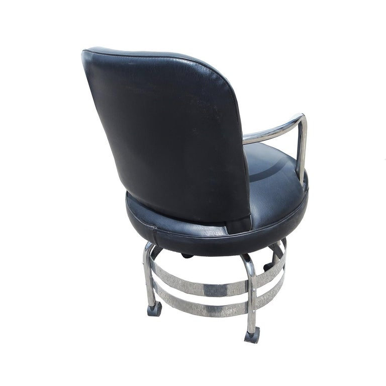 Put a little style into your workday with this fantastic Art Deco desk chair. The frame is a combination of tubular and flat banded chromed steel. The upholstery is black leatherette. The chair swivels, and will adjust in height by continued