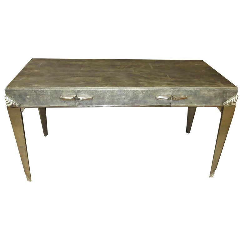 Shagreen is a leather from rays, and typically used on small decorative items such as compacts or cigarette cases. One rarely sees such an opulent use of this exotic material. The desk surfaces are all covered (top, front, sides, and back). There is