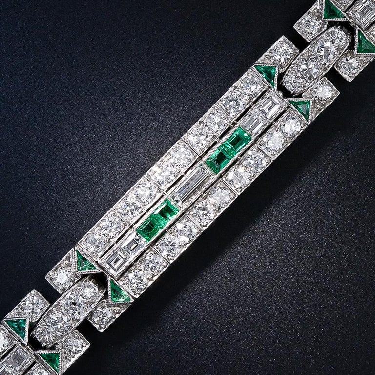 This original and quintessentially Art Deco diamond and emerald bracelet, circa 1925, radiates with bright-white and beautiful European-cut diamonds arrayed in two rows and bisected by horizontally-set baguette and square-cut diamonds which