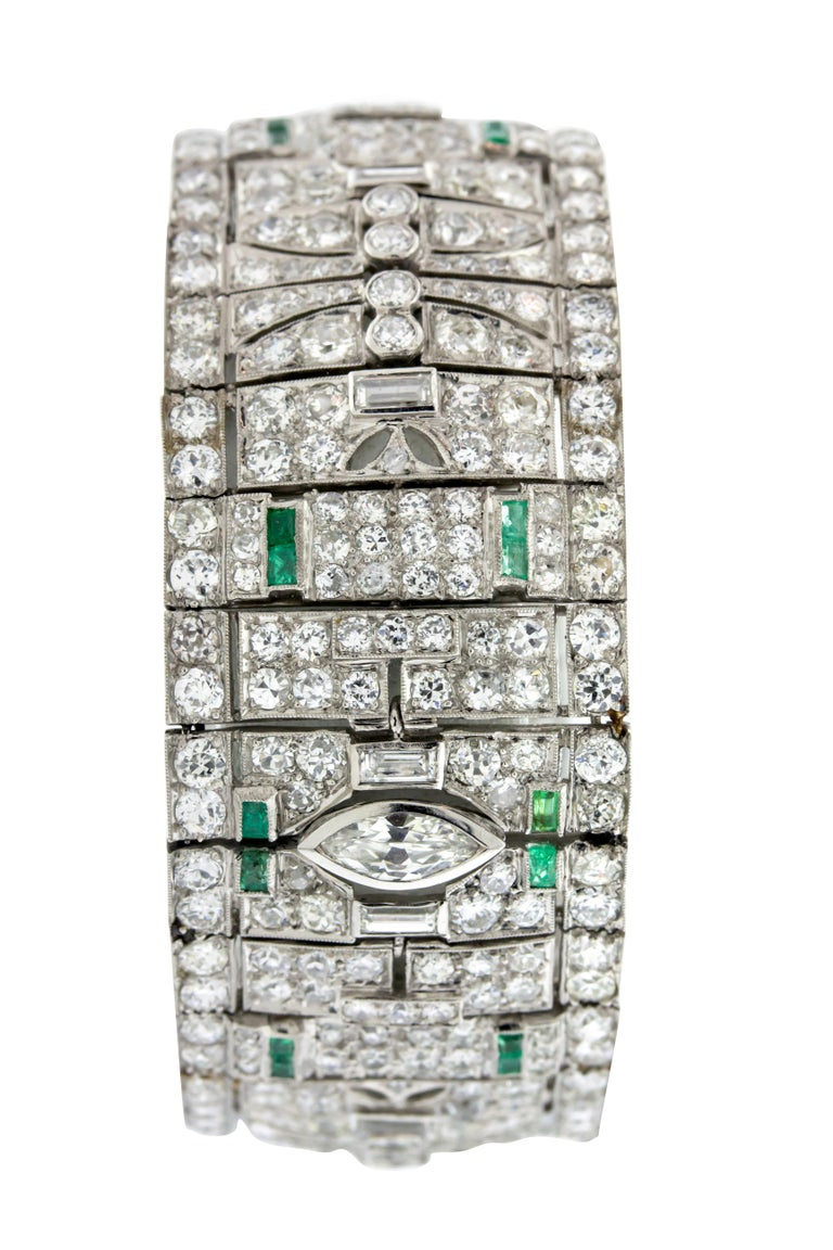 Diamond and Emerald Art Deco style bracelet circa 1930. Approximately 21 carats of mixed cut diamonds, G-H VS-I1, 1 carat emerald set in Platinum. 7 inch length, and 2.5 inches wide with a total weight of 72.8g total weight. Includes GAL