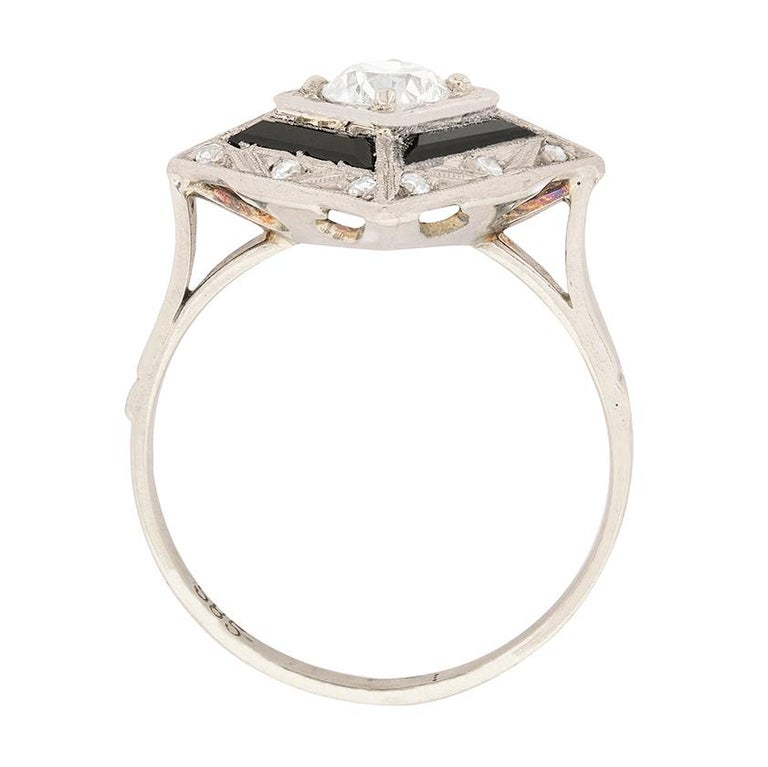 This ring, which we believe to be American because it is made in 14 carat white gold, features a 0.55 carat diamond in the centre. It is claw set and estimated as F in colour and VS1 in clarity. Surrounding is claw set onyx which is a wonderfully