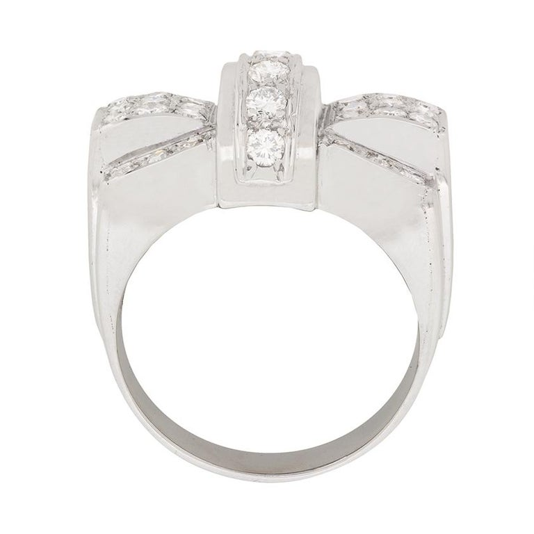 This unique and chunky cocktail ring is perfect for that special occasion. It features a bow design, with a strand of vertically set diamond in the centre, which are round brilliant. They are grain set which compliments the grain set eight cuts on