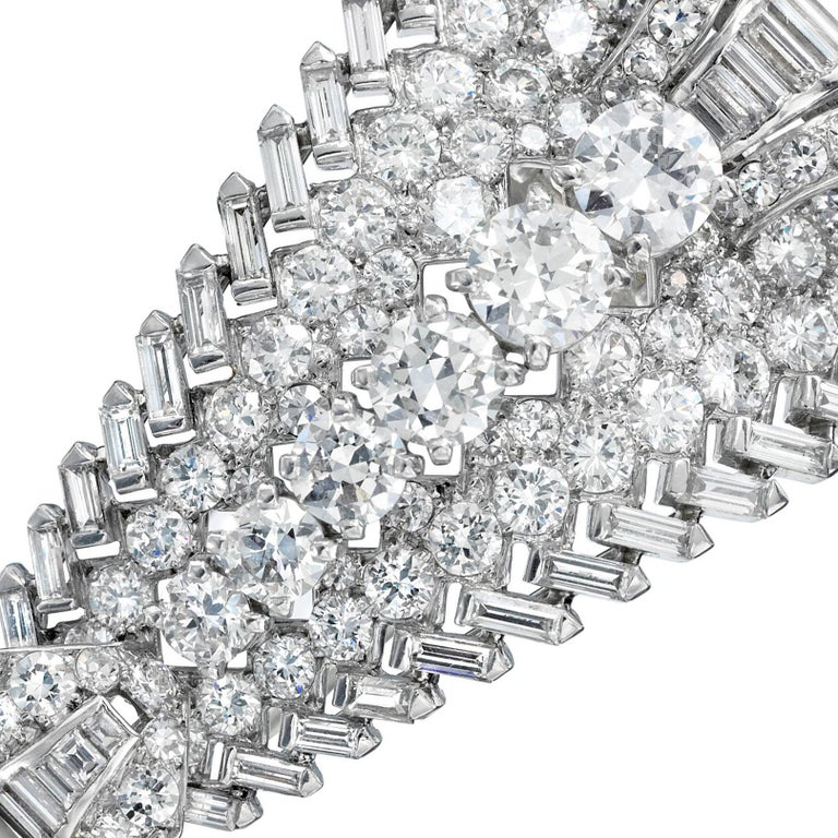 A clip brooch composed of a central line of graduated European-cut diamonds, sided by lines of European- and single-cut diamonds, edged with lines of angled baguette diamonds, the ends of the brooch curve upward and are set with diamonds, with a