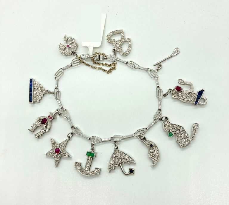 A beautiful white gold charm bracelet from the 1930s embellished with diamonds, emeralds, rubies, and sapphires.