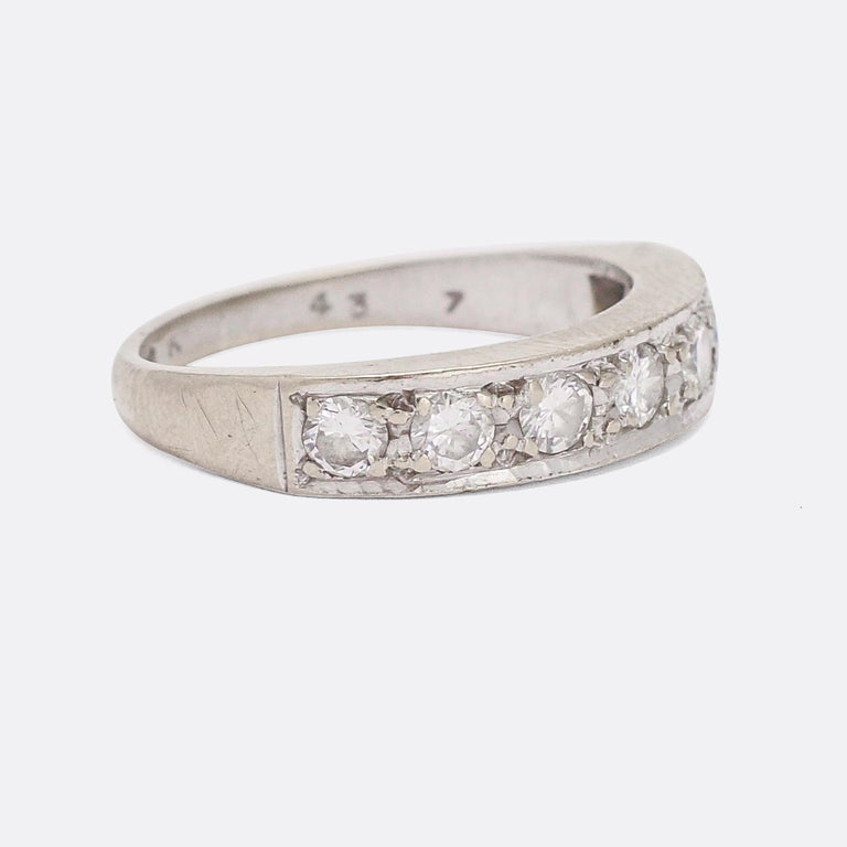 A stylish Art Deco half eternity ring set with 7 brilliant cut diamonds. It's crafted in 18k white gold with platinum settings, and dates from the 1930s. Sleek and elegant, and quintessentially Deco in style.  STONES  Brilliant cut Diamonds - total
