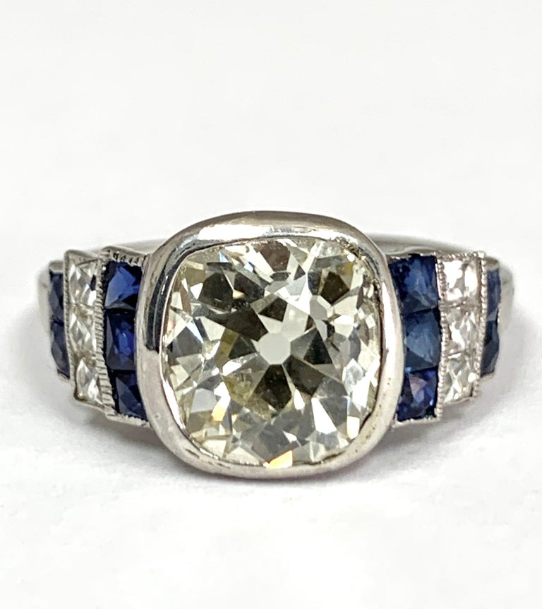 Art Deco hand made diamond engagement ring Featuring Old Euro Cut Center weighing approximately 2.57 cts. with Six french cut diamonds weighing approximately .33 cts total and  Ten french cut natural blue sapphires, weighing approximately .80 cts.