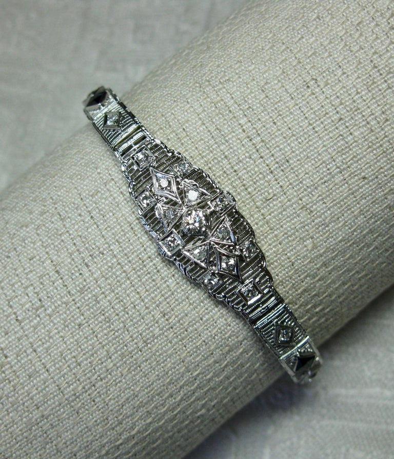 A stunning antique Art Deco Bracelet with extraordinary Deco design set with 29 high quality Diamonds totaling approximately 1.25 Carats and two fancy cut Sapphires.  The central diamond is a .20 Carat Old Mine Cut Diamond of very white H color, and