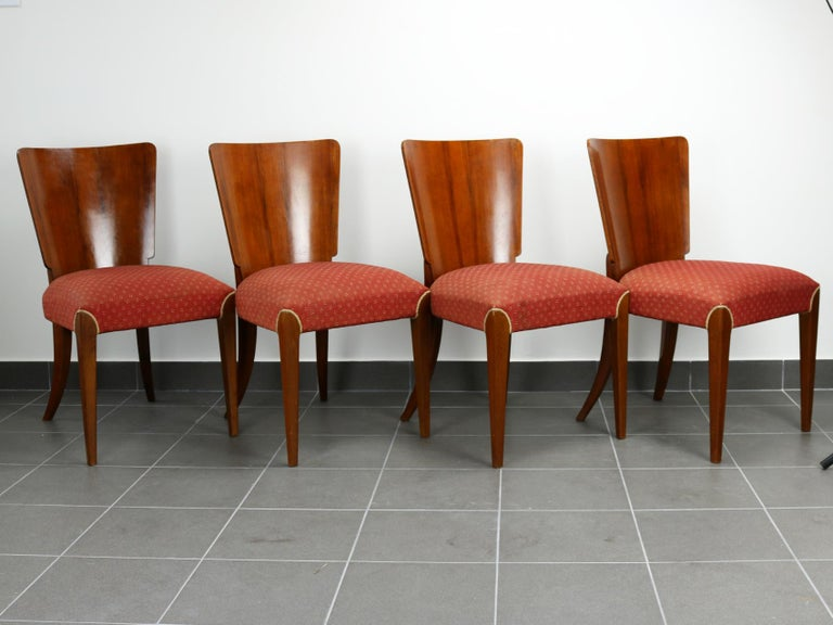 Art Deco dining chairs H214 were designed by Jindrich Halabala and manufactured in Czechoslovakia, having a beechwood frame, walnut veneer backrests, spring seats and original upholstery.