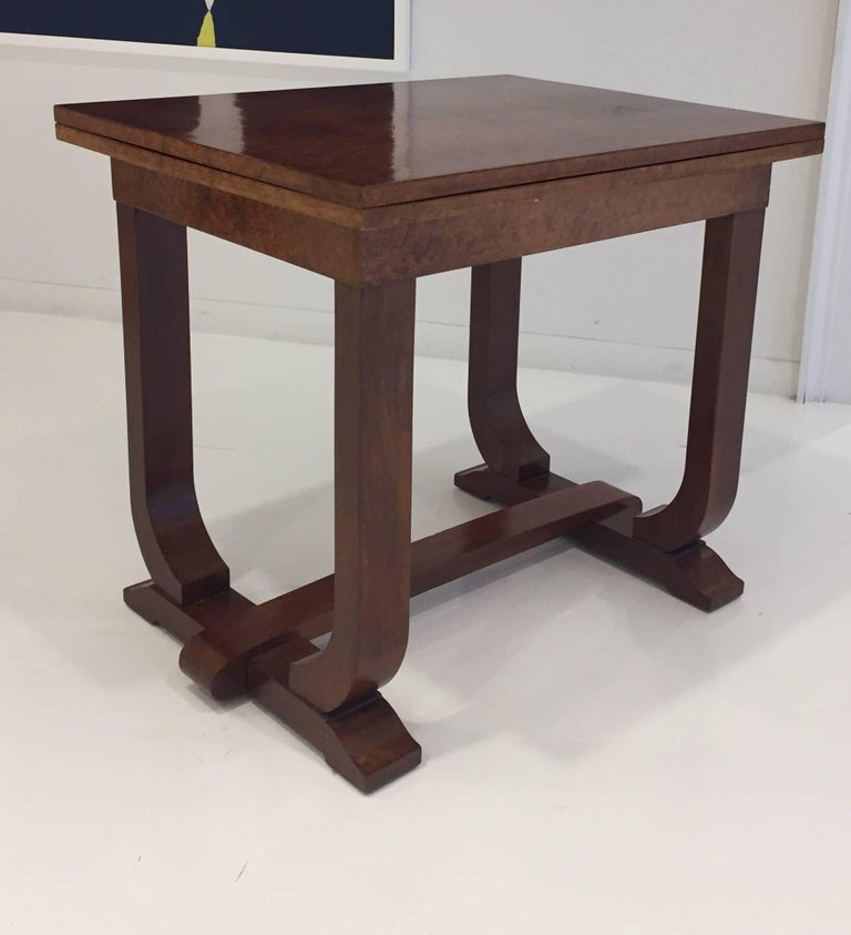 This Art Deco table is in great condition, the stylish legs in solid mahogany and the top which is in veneered burled mahogany. The table is perfect for two while it is folded closed and by opening up the folded top, the table seats four
