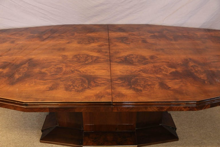 "Dining room table is made out of burl walnut. The tabletop is displaying a beauty of the wood. It supported by the wide leg, that is embellished with chrome inserts on the bottom. The table has an extra 20"" insert, which could be placed in the"