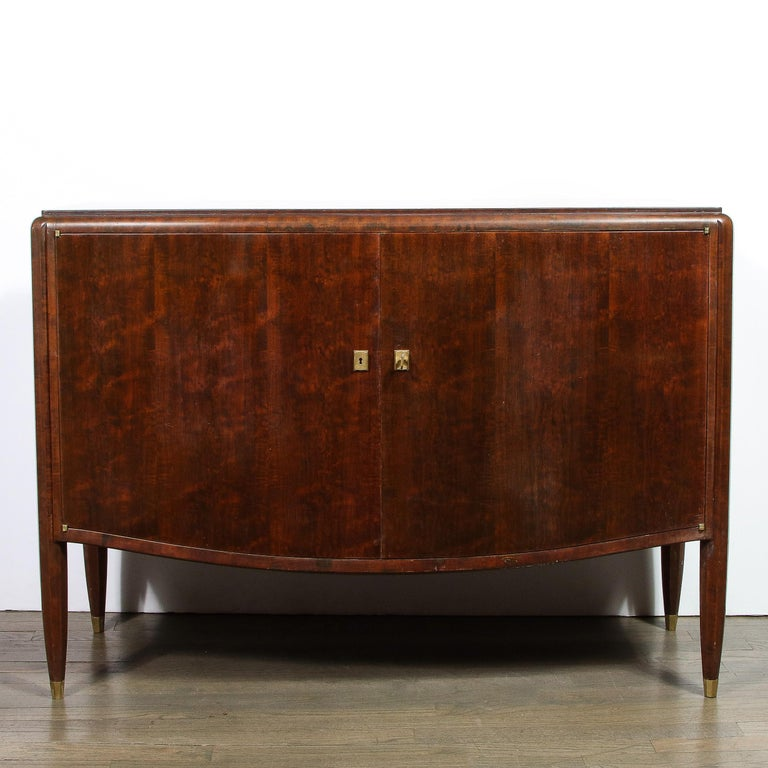 This elegant Art Deco directoire style cabinet was realized in France by the celebrated designer, Jules Leleu, circa 1940. It features a volumetric rectangular body with an undulating curved apron, as well as faceted tapered legs sitting on bronze