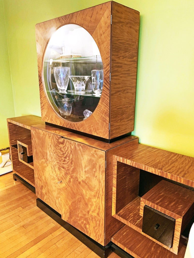 Stunning in concept and execution, this large, impressive Moderne-Art Deco cabinet consists of four parts, all centered around an internally-lit porthole vitrine with glass shelves and convex window, all finished in a golden flame mahogany that has