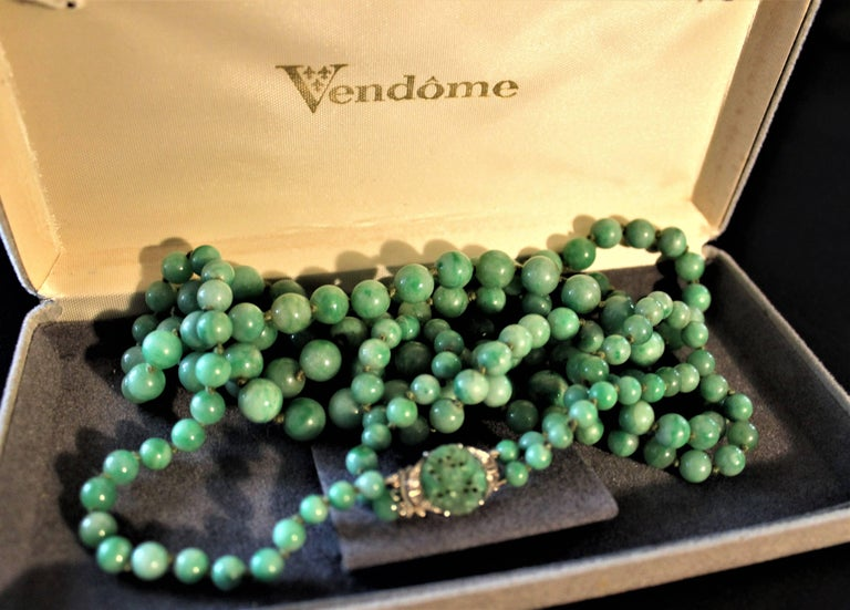 Art Deco double strand Jade hand strung graduated bead necklace with 18-karat gold, four diamonds and Jade on clasp. Measures: 27 inches long double strand, 14 inches tied.