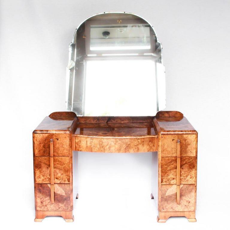 An Art Deco dressing table with drawers to centre and both sides. Shaped, arched, original mirror. Burr walnut throughout. 