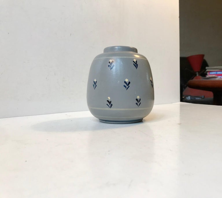 Small grenade shaped earthenware vase with elefant grey main paint and hand decorated with small flowers. It was made by Knabstrup in Denmark during the 1920s or 1930s in a style derived from French and German Art Deco era pottery.