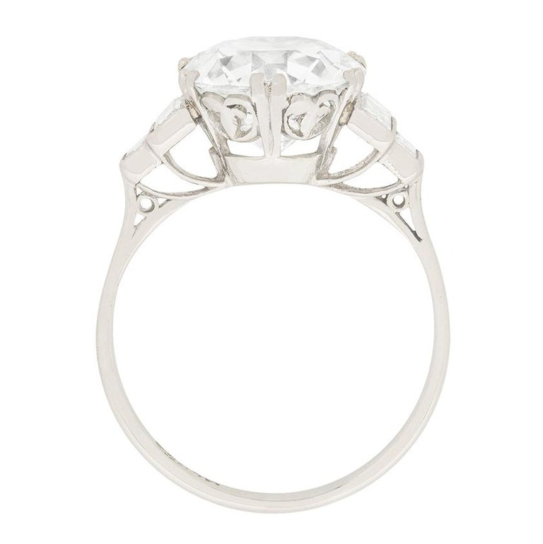 Stepped shoulders set with diamond baguettes lead to a dramatic EDR certified, 3.67 carat, transitional cut diamond at the centre of this original Art Deco engagement ring  In quintessential 1920s fashion, double claws secure the principal stone