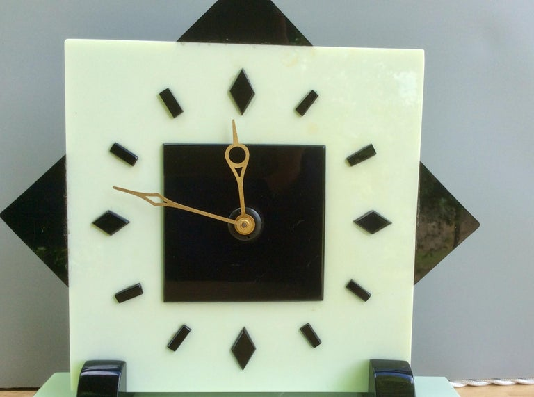 Art Deco timepiece  Art Deco electric timepiece in a light green and black Bakelite case standing on rectangular shaped feet and resting on a stepped two color plinth.  Square dial with baton markers and gilded hands.  Electric movement by