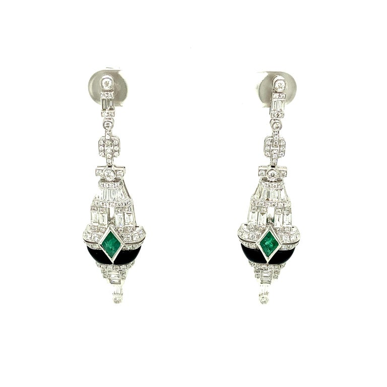 Art-Deco Style Emerald, Black Onyx, and White Diamond Gold Dangle Earrings:  A beautiful pair of earrings, it features two kite shaped emeralds weighing 3.63 carat, with a stunning arrangement of white diamonds weighing 2.23 carat, and tubular black