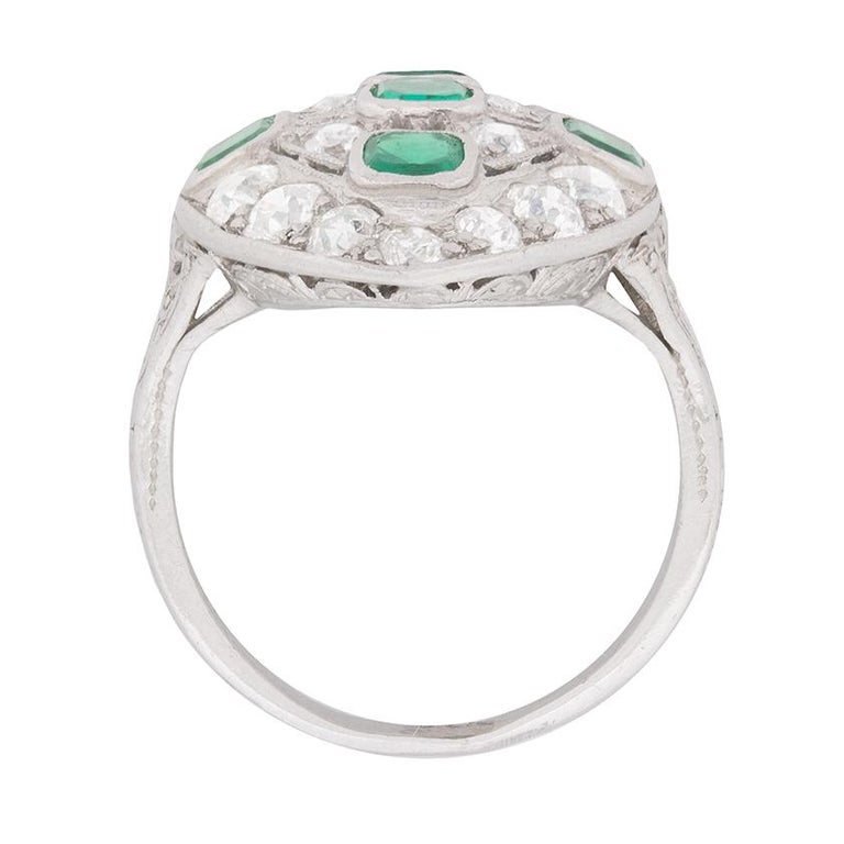 Five old cushion cut emeralds diamonds in a bright shade of green comprise the horizontal and vertical centre of this original Art Deco dinner ring.  Millegrained openwork detailing separates the emeralds, which are rub over set in box collets and