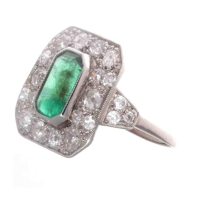 An expression of the glorious times that were to be known as the art deco time period. A time of extravagance and luxury. Featuring a glowing green emerald surrounded by a shield of diamonds. Hand crafted in platinum.  Ring size 7 and can easily be