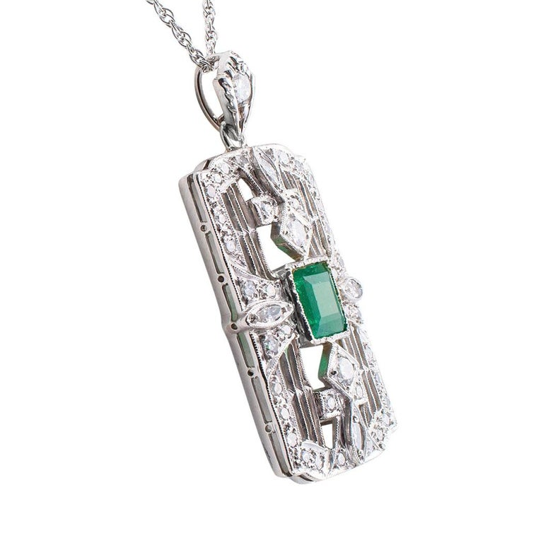 Art Deco emerald diamond platinum and white gold pendant necklace circa 1930.  The rectangular design centers upon a square emerald weighing approximately 1.00 carat, within a wide border of milgrained wire work and geometric motifs set with