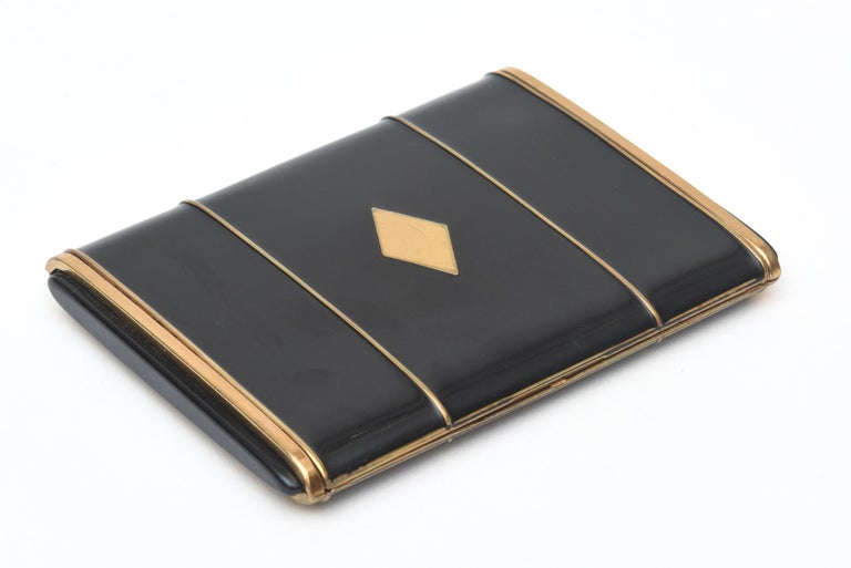 This stunning period art deco card case was once a cigarette case from the era. it is black enamel and gold metal with a diamond center form. This makes now a great holiday gift. It should be kept in a jewelers bag in one's handbag so there are not
