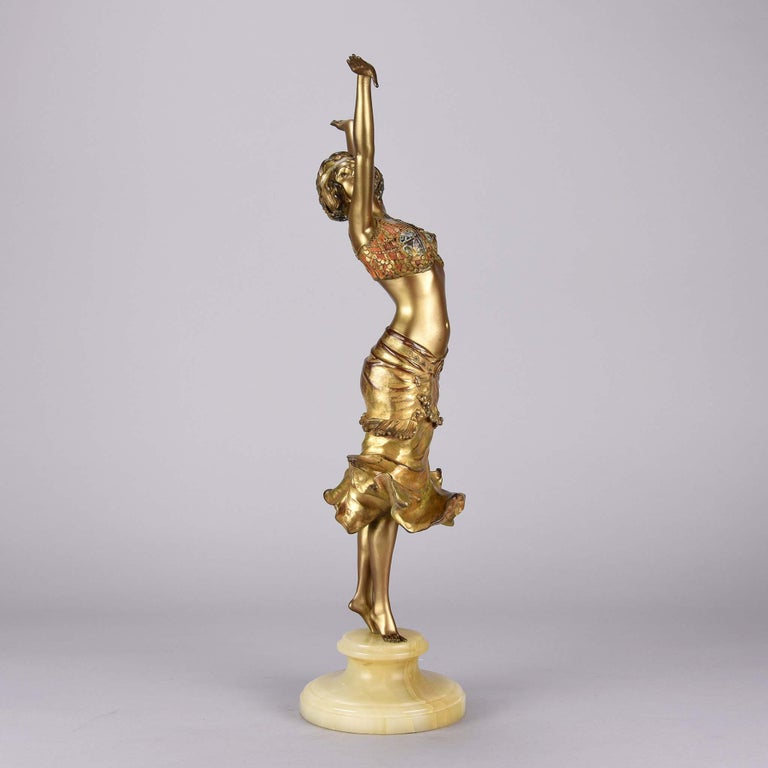 An extremely fine French early 20th century Art Deco bronze figure of a young attractive woman in a two piece costume poised on her tip toes with both hands raised above her head, the costume with rich red, gold and silver cold painted enamel