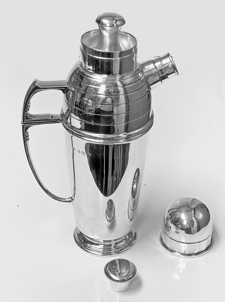 """Art Deco English silver cocktail shaker, Birmingham 1913 Pearce & Sons. The cocktail shaker of plain cylindrical form on spreading plain circular footed base, with large """"C"""" style handle with solid mid-section, the upper body of the Shaker with"""