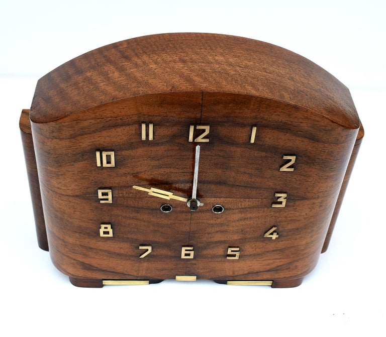 For your consideration is this English free standing 1930s Art Deco mantle clock. The case is made from Walnut and is embellished with brass Art Deco stylized numerals which are in relief. The movement is eight day and strikes on the hour. We've had