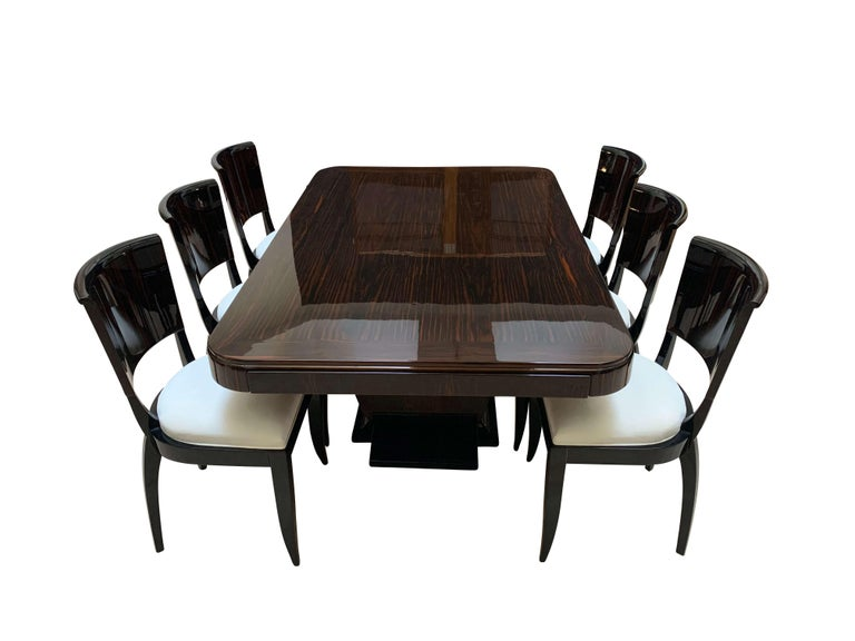 Beautiful Art Deco Dining Room Set in Macassar from France around 1925.   The set consists of one expandable dining table and six chairs.   Wonderful Macassar ebony wood (dark red-brownish tone) veneered and lacquered in several layers of clear and