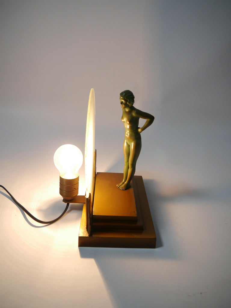 Art Deco figure lamp, showing a seminude bronze female figure standing on a podium and leaning towards a frosted glass screen. The figure can also be turned around 180 degrees. The figure shows delicate detailing and beautiful age related patina.