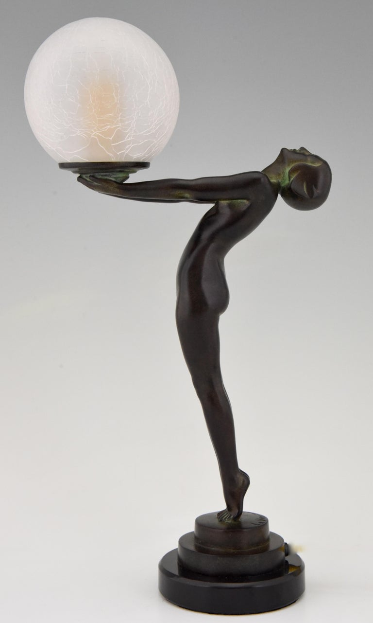 Art Deco figural table lamp of a standing nude lady holding a glass globe. This model is called Lueur lumineuse and is the smaller version of the iconic Clarté lamp by Max Le Verrier. The lamp is signed and has the Le Verrier foundry mark. Designed