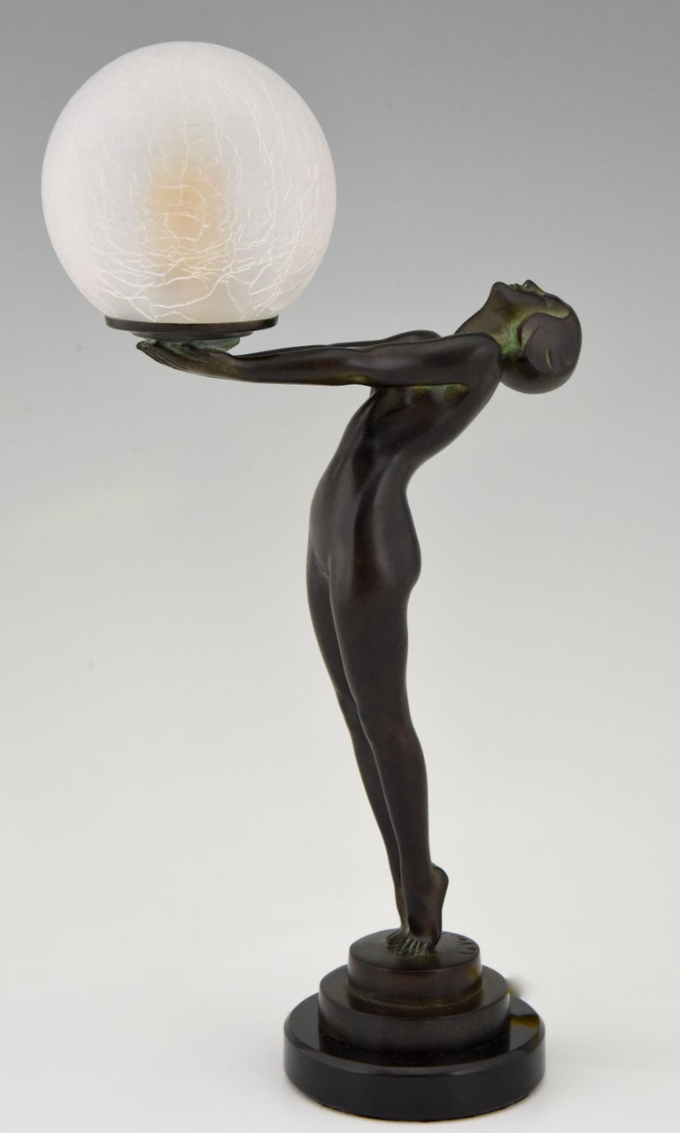 Patinated Art Deco Figural Lamp Standing Nude Holding a Glass Shade Max Le Verrier Clarté For Sale