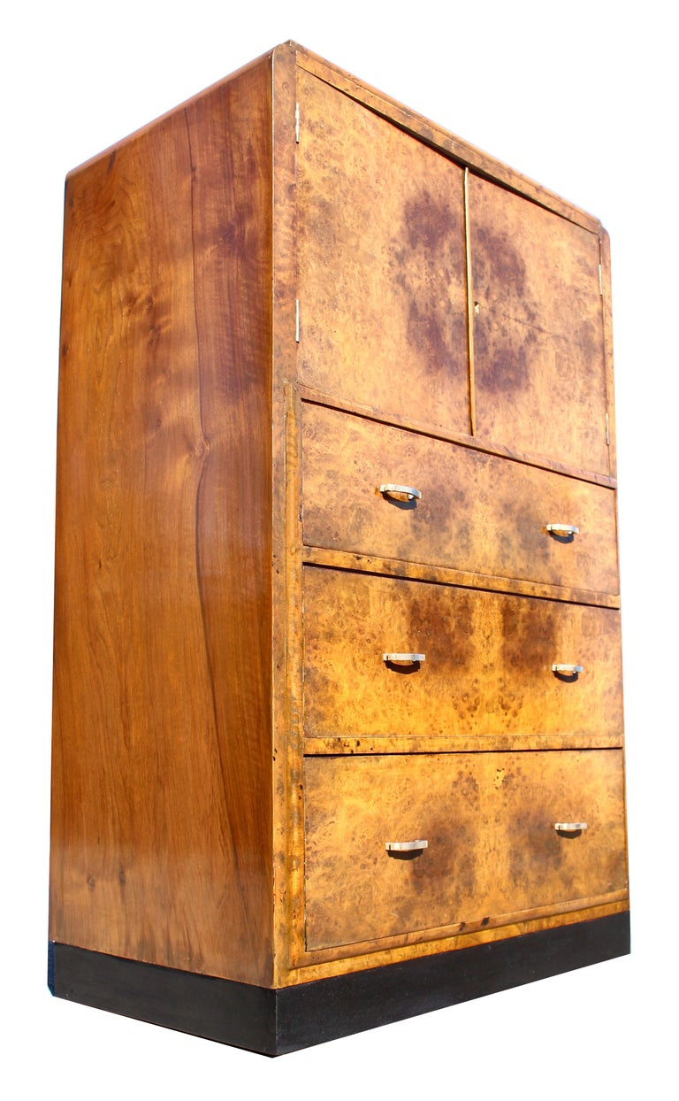 For your consideration is this English Art Deco honey coloured walnut two-door, three drawer single-piece tallboy, circa 1930, boasting stunning mirror matched veneers and in excellent original condition. All resting on a ebonised plinth. The