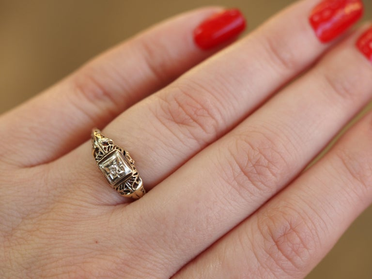 This Art Deco solitaire is a fine example of a filigree solitaire engagement ring crafted in 10 karat white & yellow gold. The 0.03 ct Single cut diamond is held high in four prongs showcasing the solitaire from all sides! The filigree design twists