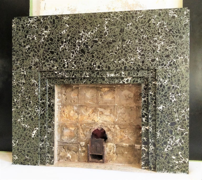 An Art Deco fireplace from the 'Rouring Twenties': 1921-1939. The formal lines ànd the striking marble, provides a subdued, quite ambiance. It shows luxury in an artistic atmosphere. Art Deco is characterized by color, geometric figures, zig-zag