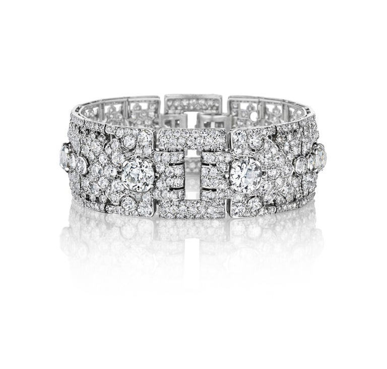 A wide flexible band bracelet set with diamonds, created in two hinged segments each set with a line of larger raised diamonds on a pave ground with pierced elements near the edges; mounted in platinum • 568 diamonds, total weighing approximately